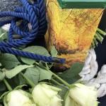 Ashouder-staat-opgebaard-met-touw-en-bloemengroet