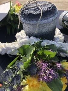 Zee-urn-opgebaard-met-bloemengroet-en-touw